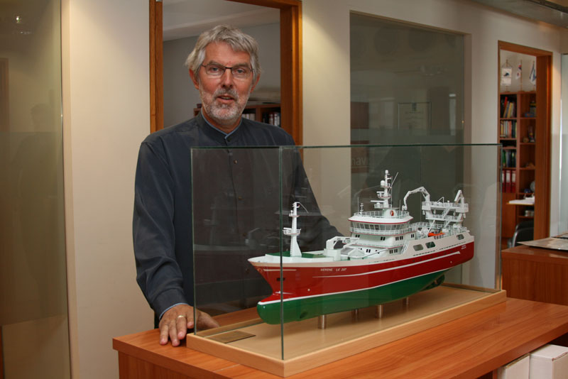 Hjörtur Emilsson next to a model of one of the vessel Navis has taken part in designing.